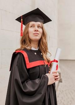 Menina de baixo ângulo com diploma