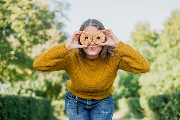 Menina de baixo ângulo com donuts ao ar livre