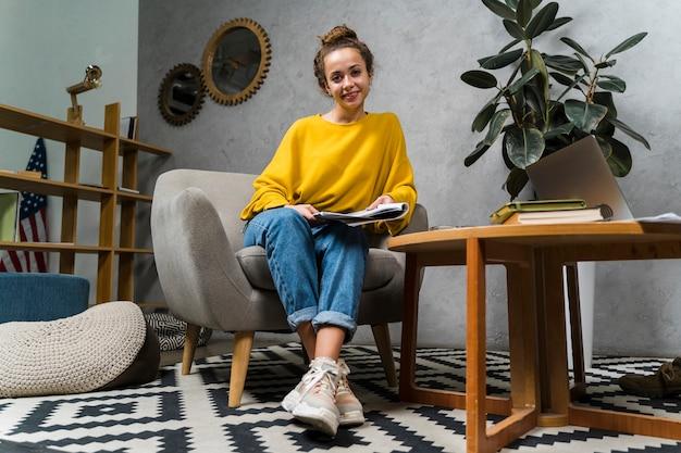 Menina de baixo ângulo com notebook dentro de casa