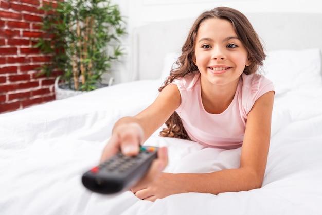 Menina de baixo ângulo na cama segurando o controle remoto