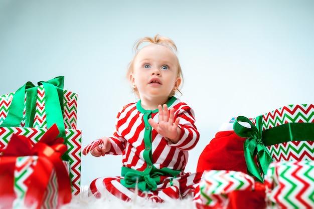 Menina de bebê fofo 1 ano de idade perto de chapéu de papai noel, posando no natal com decoração. sentado no chão com uma bola de natal