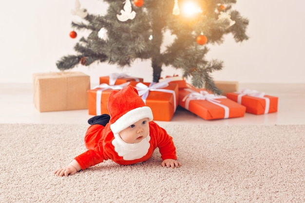 Menina de bebê fofo vestindo terno de papai noel, rastejando no chão, sobre a árvore de natal. temporada de férias.