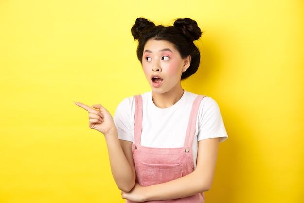 Menina de beleza asiática intrigada com maquiagem, olhando curiosa para o logotipo, apontando o dedo de lado, em pé com roupas de verão contra amarelo.
