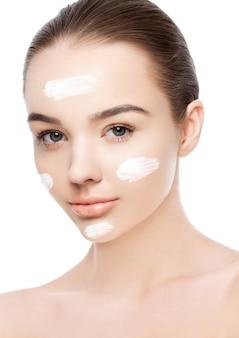 Menina de beleza com maquiagem natural de creme para o rosto