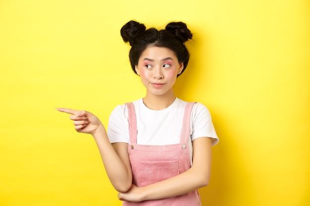 Menina de beleza fofa com maquiagem e roupas de verão, apontando e olhando para a esquerda no banner promo, curioso em amarelo.