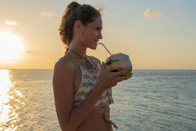 Menina de beleza jovem bebendo coco na praia tropical perto da água do mar, na ilha do paraíso ao pôr do sol, close-up. conceito de verão. viagem de férias.
