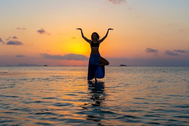 Menina de beleza jovem dançando na praia tropical na água do mar, na ilha do paraíso ao pôr do sol, close-up. conceito de verão. viagem de férias.