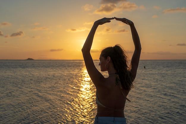 Menina de beleza jovem dançando na praia tropical perto da água do mar, na ilha paradisíaca ao pôr do sol, close-up. conceito de verão. viagem de férias.