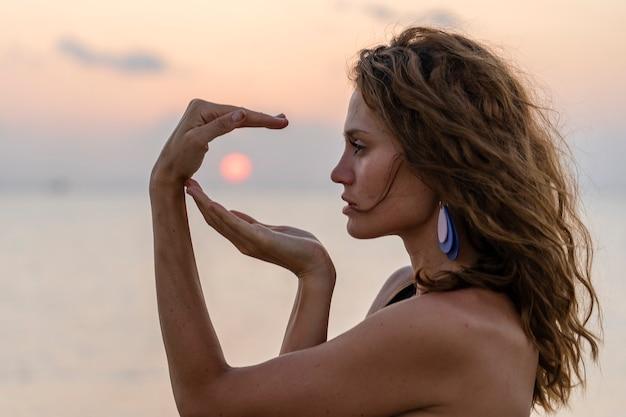 Menina de beleza jovem na praia tropical de mãos dadas ao redor do sol na ilha paradisíaca ao pôr do sol, close-up. conceito de verão. viagem de férias.