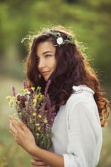 Menina de beleza natural com buquê de flores ao ar livre no conceito de gozo de liberdade. foto de retrato