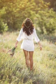 Menina de beleza natural com buquê de flores ao ar livre no conceito de gozo de liberdade.