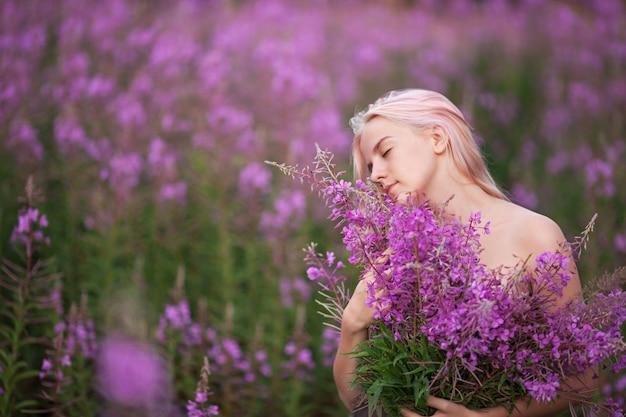 Menina de beleza romântica ao ar livre. bela modelo adolescente com garota de cabelo rosa no campo de fireweed no nascer do sol.