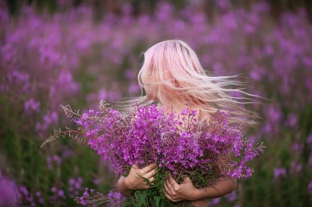 Menina de beleza romântica ao ar livre. menina linda modelo adolescente com cabelo rosa no campo de fireweed no nascer do sol. soft fokus