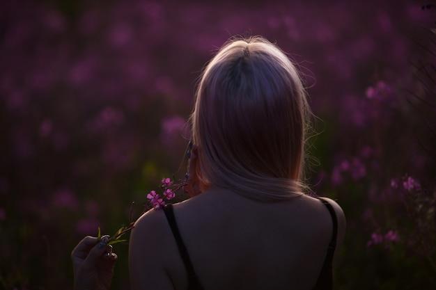 Menina de beleza romântica ao ar livre. menina linda modelo adolescente no campo de fireweed no nascer do sol. vista traseira