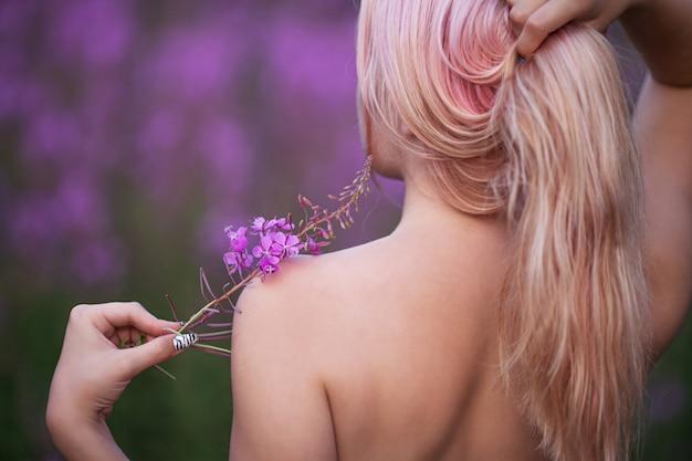 Menina de beleza romântica ao ar livre. menina linda modelo adolescente no campo de fireweed. vista traseira. ombros e costas nus.