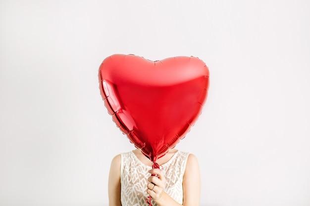 Menina de beleza segurando um balão de forma de coração vermelho. conceito de amor