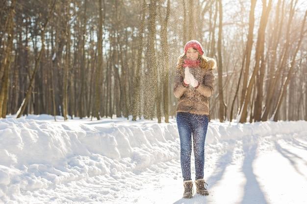 Menina de beleza soprando neve no parque de inverno gelado. ao ar livre. flocos de neve voadores.