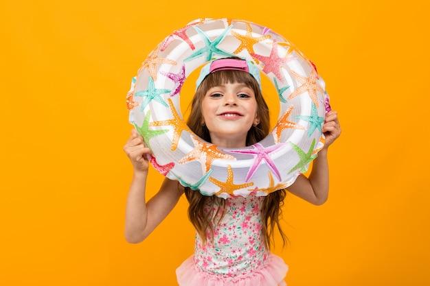 Menina de biquíni com um círculo de natação em uma parede laranja