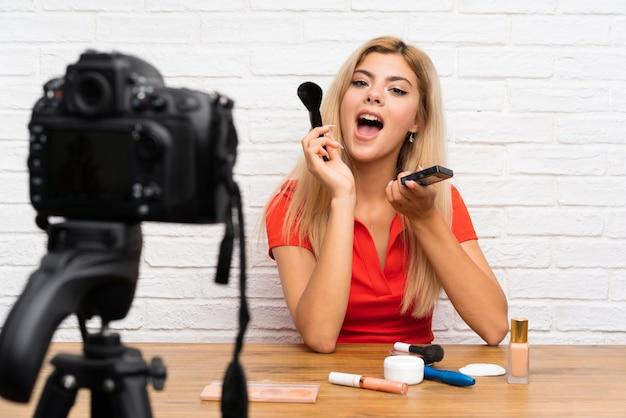 Menina de blogueiro adolescente gravando um tutorial em vídeo