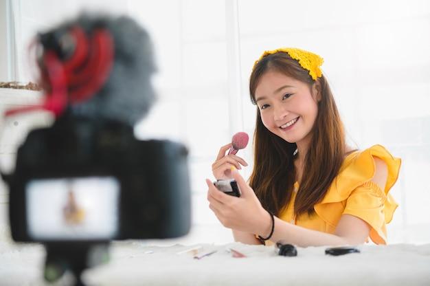 Menina de blogueiro de beleza jovem asiática feliz treinando como ser artista de maquiagem em estúdio em casa