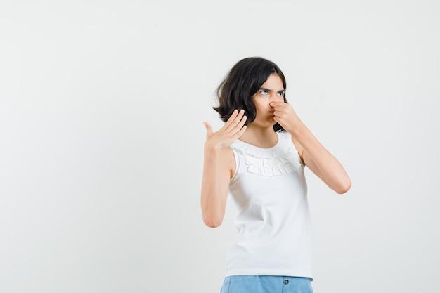 Menina de blusa branca, shorts apertando o nariz devido ao mau cheiro e parecendo enojada, vista frontal.