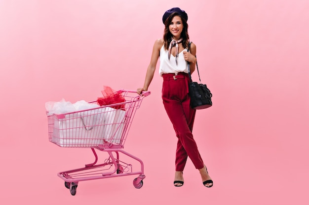 Menina de boina está sorrindo e posando com carrinho rosa. linda senhora em calças clássicas cor de vinho e blusa branca rindo.