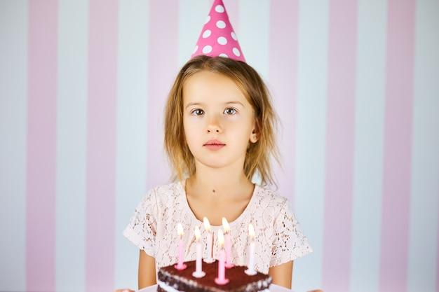 Menina de boné de aniversário rosa com bolo de chocolate com velas