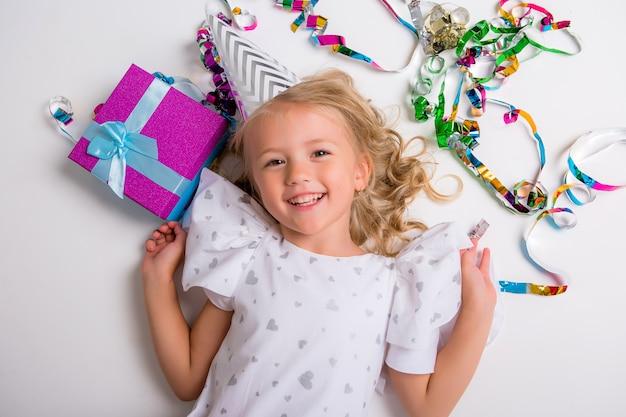 Menina de boné de aniversário sorrindo com confete e caixa de presente