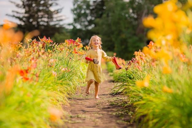 Menina de botas de borracha vermelha e um chapéu de palha regar flores vermelhas de rega no jardim