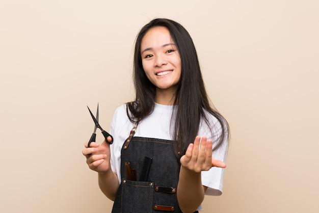 Menina de cabeleireiro adolescente convidando para vir com a mão. feliz que você veio