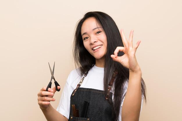 Menina de cabeleireiro adolescente mostrando sinal de ok com os dedos