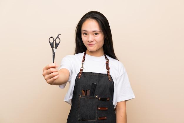 Menina de cabeleireiro adolescente sobre parede isolada