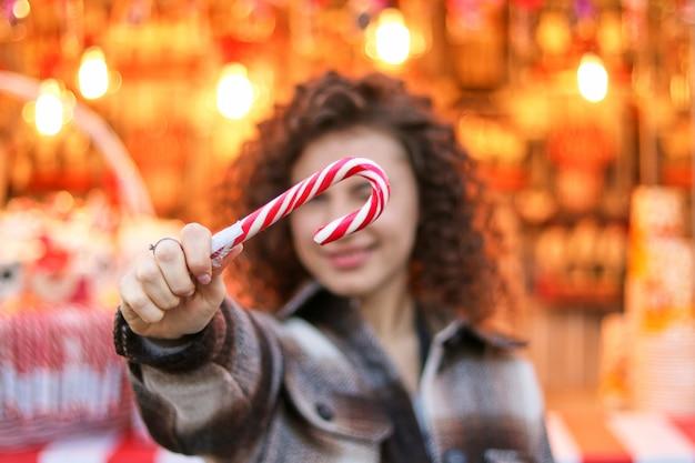 Menina de cabelo encaracolado bonito segurando o bastão de doces na feira