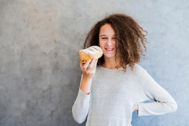 Menina de cabelo encaracolado cura comer croissant