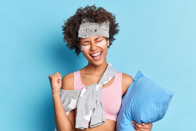 Menina de cabelo encaracolado muito feliz fecha os punhos de alegria comemora finalmente alcançando seus objetivos descobre notícias positivas usa roupa de dormir tem expressão alegre segura travesseiro isolado na parede azul