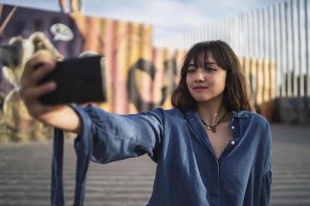 Menina de cabelo preto tirando uma foto dela atrás de um prédio