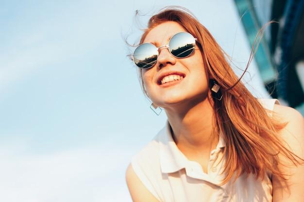 Menina de cabelo vermelha feliz bonita positiva nos óculos de sol do espelho