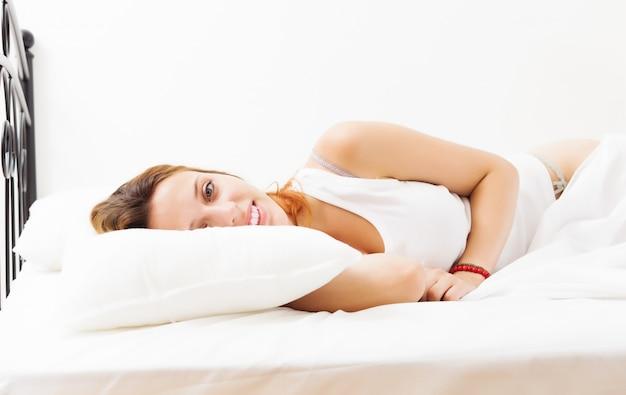 Menina de cabelo vermelho alegre deitada na folha branca