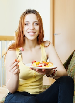 Menina de cabelo vermelho comendo salada de frutas