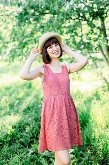 Menina de cabelo vermelho lindo fica no fundo jardim maçã ela segura o chapéu no chapéu e sorri um sorriso doce. a garota está vestida com um vestido azul, com bolinhas brancas e um chapéu de palha no panamá.