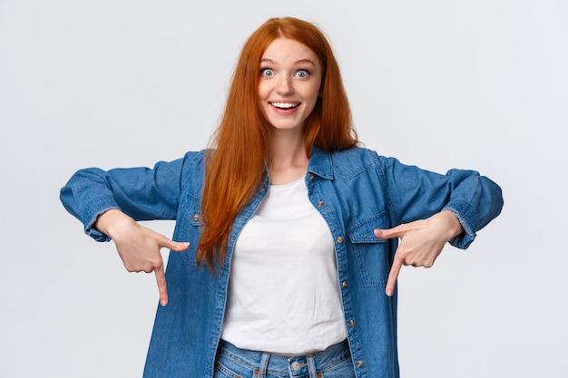 Menina de cabelo vermelho sorrindo fascinada apontando os dedos para baixo