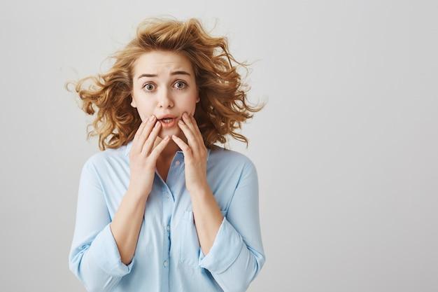 Menina de cabelos cacheados preocupada e assustada ofegando preocupada