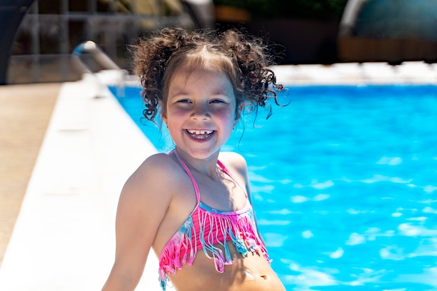 Menina de cabelos cacheados rindo à beira da piscina