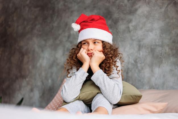 Menina de cabelos cacheados tween infeliz linda de chapéu de papai noel e pijama, sentada na cama com travesseiro, tempo de manhã de natal