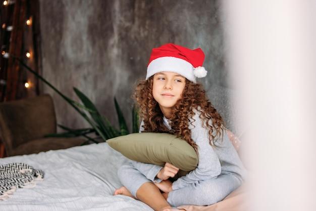 Menina de cabelos cacheados tween linda no chapéu de papai noel e pijama, sentada na cama com travesseiro, tempo de manhã de natal