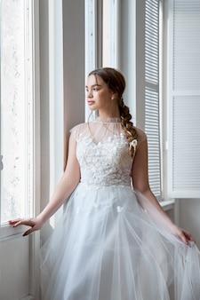 Menina de cabelos castanho em um lindo vestido de noiva branco. noiva mulher está esperando o noivo antes do casamento
