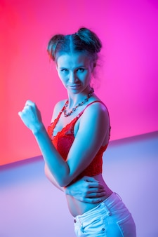 Menina de cabelos compridos atraente, moda elegante. criativo colorido néon retrato. menina bonita uma roupa interior vermelha e calças de brim que levantam. retrato da noite cinematográfica de mulher em neon.
