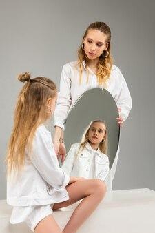 Menina de cabelos compridos em roupas brancas olhando seriamente para ela refletindo enquanto a irmã mais velha carregava um espelho