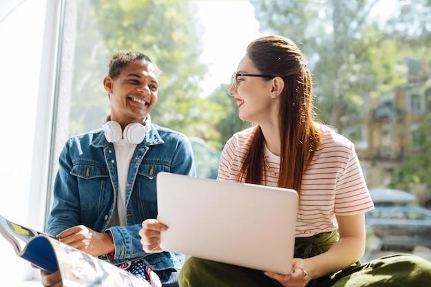 Menina de cabelos compridos satisfeita com um sorriso no rosto enquanto ouve seu parceiro