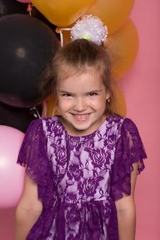 Menina de cabelos escura com balões coloridos em fundo rosa